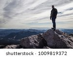 man stands on top of mountain... | Shutterstock . vector #1009819372