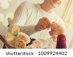 young man putting on girlfriend ... | Shutterstock . vector #1009924402