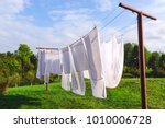 Stock photo fresh clean white sheet drying on washing line in outdoor 1010006728