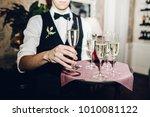 waiter brings glasses of... | Shutterstock . vector #1010081122