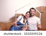 Small photo of Portrait of a couple in love who have just bought a house and is moving. The bride and groom smile and hold the house-shaped meter in their hands. Concept of: future, family, mortgage and loan.