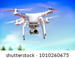 white quadrocopter is flying... | Shutterstock . vector #1010260675