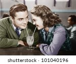 Couple in a restaurant looking at each other and sharing a milk shake with two straws - stock photo