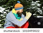 Small photo of Macho with beard and mustache pats dog. Man wears knitted hat, scarf and gloves with black dog. Guy with firtrees covered with snow on background, defocused. Friendship and allegiance concept.