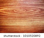 Small photo of Background. Cross section of the tree. Contrast texture. Polished wood. Colors from dark red to light yellow. Annual rings are allocated. Inhomogeneous structure.