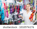 Stock photo happy female shop assistant showing leashes for pets in pet shop 1010576176