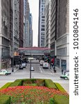 Small photo of CHICAGO, IL - MAY 5, 2011 - View of Madison St. intersection with Michigan Ave, next to Millenium Park, during spring, with trees in full blossom