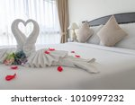 Small photo of White swan folded towel, Symbols of single-minded love. Set in a white bed for couples in a romantic and warm atmosphere.