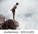 female swimmer on rock above... | Shutterstock . vector #101111692