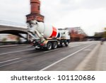 city street with a driving cement truck - stock photo