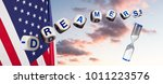 Small photo of Dreamers children spelling letters on sunset sky and USA flag with hourglass to suggest urgency