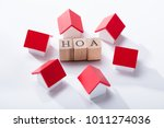 Small photo of Homeowner Association Wooden Blocks Surrounded With Miniature House Models Over The White Background