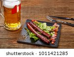 grilled sausages with beer on... | Shutterstock . vector #1011421285