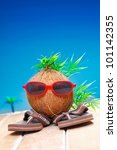 Small photo of Trendy coconut with foliage hairstyle and natty red sunglasses wearing slip slops as he goes on his travels