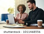 smiling work colleagues sitting ... | Shutterstock . vector #1011468556