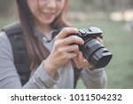 Woman holding mirrorless camera travel photo of photographer Making pictures in hipster style