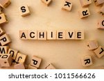 Small photo of Achieve word cube on wood background