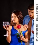 Small photo of Couple drink red wine glass together. Woman hold rose flower. Man undresses his beloved woman. Relations without obligations. Acquaintance in a night club.
