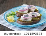 Stock photo herring fillets in a white plate on a dark wooden table soft focus 1011593875