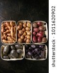 Small photo of Variety of raw uncooked organic potatoes different kind and colors red, yellow, purple in market baskets over dark texture background. Top view, space