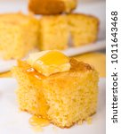 Stock photo piece of freshly baked cornbread with butter and honey dripping off the top 1011643468