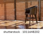 Small photo of Room interior sunlight through blinds bamboo curtain widow with wood flooring and wood chair in nature minimal style