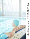 Small photo of Young lad in swimwear leaning against swimming-pool while enjoying rest in water