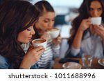 three young women enjoy coffee... | Shutterstock . vector #1011688996