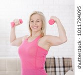 happy middle aged woman lifting ... | Shutterstock . vector #1011734095