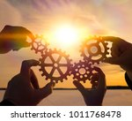 four hands collect the gear... | Shutterstock . vector #1011768478