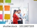 three colleagues brainstorming... | Shutterstock . vector #1011807205