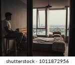 Small photo of Lonely and spiritless Asian man is sitting in his bedroom looking at sunset with smartphone on his hand.
