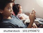 asian kids using smart phone in ... | Shutterstock . vector #1011950872