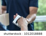 customer is signing on phone... | Shutterstock . vector #1012018888