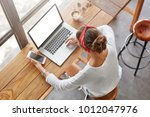 Small photo of Top view of fashionable femle student learns online on laptop computer, prepares for classes or exam, holds cell phone as waits for call, spends free time at cafeteria with mug of tasty latte
