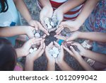 Small photo of Group of children holding money in hands in the circle together as finance and charity concept