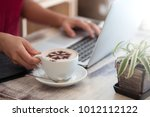 laptop and a cup of coffee in... | Shutterstock . vector #1012112122