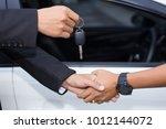 car salesman handing over the... | Shutterstock . vector #1012144072