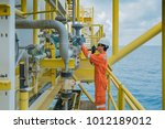 Small photo of Offshore oil and gas worker operating touch screen of gas flow meter coriolis type to reading and adjusting parameter of flow element and used radio to talk with central control room operator.