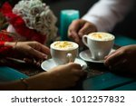 couple drinking coffee at a... | Shutterstock . vector #1012257832