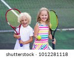 boy and girl playing tennis on...   Shutterstock . vector #1012281118