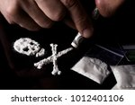 Small photo of Drug dependence Kills. Junkie man sniffing a line of cocaine in the shape of a skull through a dollar, sachets with a dose. Black background. Narcotics concept.