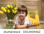 a small child with a bouquet of ... | Shutterstock . vector #1012405462