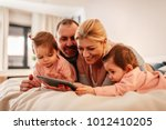 parents lying on bed with two... | Shutterstock . vector #1012410205