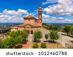 Small photo of Old brick parish church under beautiful blue sky with white clouds in small town of Diano d'Alba in Piedmont, Northern Italy.
