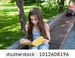 cute teenage girl reading book... | Shutterstock . vector #1012608196