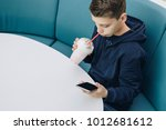 teenager boy sits at table in... | Shutterstock . vector #1012681612