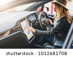 young woman sits behind wheel...   Shutterstock . vector #1012681708
