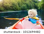 child with paddle on kayak.... | Shutterstock . vector #1012694482