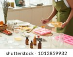woman adding dry orange slices... | Shutterstock . vector #1012859932